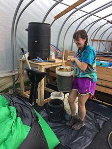 Gabbie Batzko loading the digester