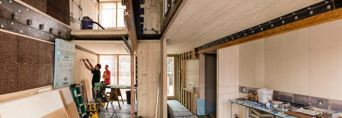 inside of a partially built house, students working in the background