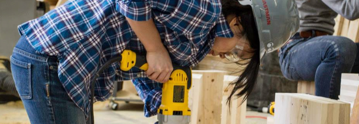 Student in hard hat using a drill