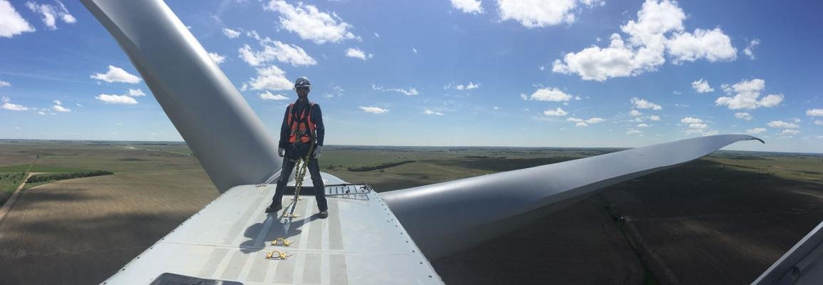student on top of large wind turbine