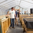 Inside the greenhouse, thermal battery (left) and raised aquaponics grow beds (right)